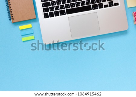 Home office desk with laptop, kraft notepad, sticky notes on a blue pastel background #1064915462