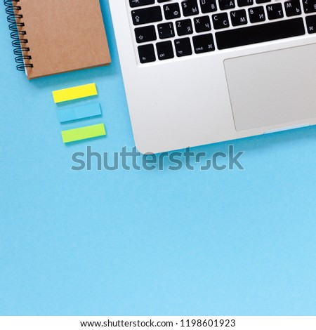 Home office desk with laptop, kraft notepad, sticky notes on a blue pastel background #1198601923