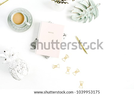 Home office desk. Workspace with pale pastel pink notebook, coffee and decorations on white background. Flat lay, top view. #1039953175
