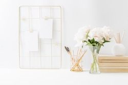 Home office desktop and mood board with empty card, white peonies in a vase, office supplies on a light background. Home interior or office background
