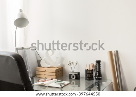 Home office in new style with glass desk and comfortable chair.