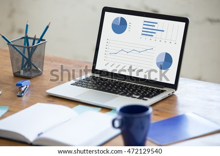 Home office interior in loft space. Workplace with wooden table, office supplies, documents, organizer and laptop. Modern office workplace. Focus on laptop screen with charts and diagrams