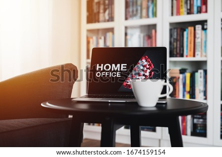 Home office theme. Home office during coronavirus pandemic. Novel coronavirus 2019 COVID-19 theme. Coronavirus wallpaper on computer. Coffee Cup in foreground.