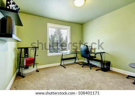 Home office with beige carpet and simple furniture.