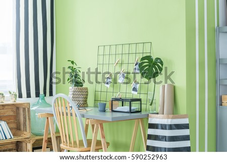 Home office with green plants, desk, chair and metal accessories