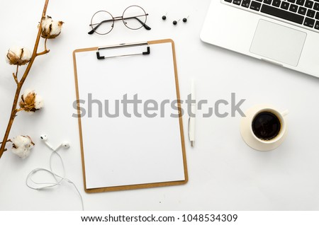 Home office workspace mockup with laptop, clipboard, cotton, coffee, headphones, glasses and accessories. Flat lay, top view. Template for blog, bloger, business