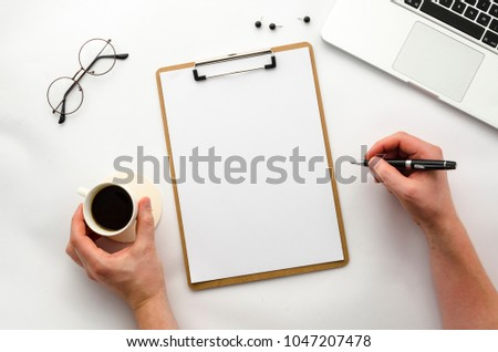 Home office workspace mockup with laptop, clipboard, notebook and accessories.Man writes on clipboard. Male hands holding a pen and coffee. Flat lay, top view