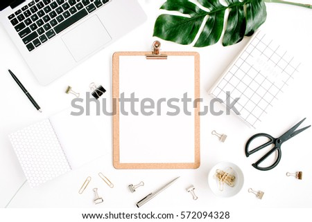 Home office workspace mockup with laptop, clipboard, palm leaf, notebook and accessories. Flat lay, top view