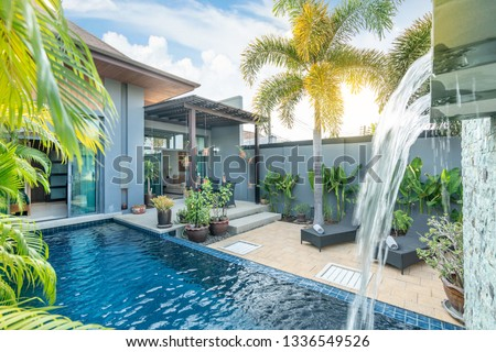 home or house building  Exterior  and interior design showing tropical pool villa with green garden, with sun bed and blue sky  #1336549526