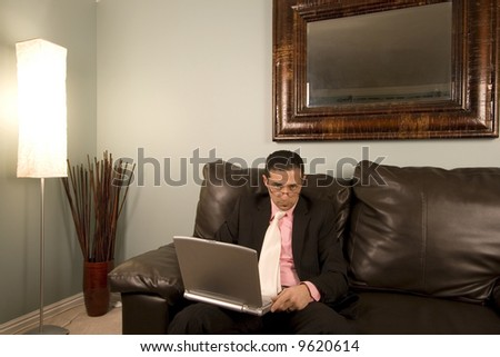 Home or Office - Businessman Looking over His Glasses on the Couth