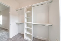Home organization ideas with view of an emplty closet for storing of clothes. Shelves and two level clothes rods are built in against the clean white wall of house.