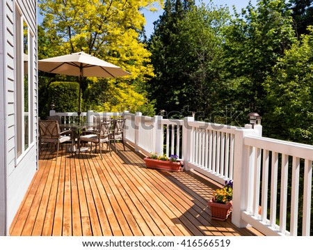 Home outdoor cedar deck with furniture and open umbrella during nice bright day. Horizontal layout.  #416566519