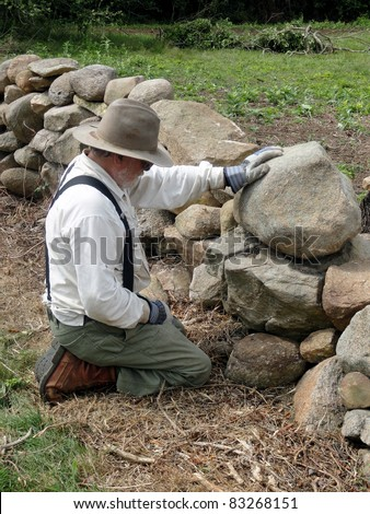 Home owner building a stone wall on his property. #83268151