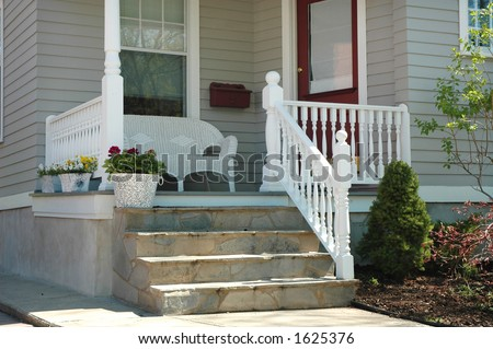 Home porch with white wicker seat, front door entrance, steps, planter