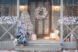 Home porche decorated with snow covered branches of a Christmas tree. Christmas decor, snowy mood, winter still life.