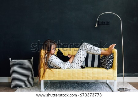 Home portrait of pre teen child girl wearing pajama hugging her cat on the yellow couch against black wall in modern living room interior