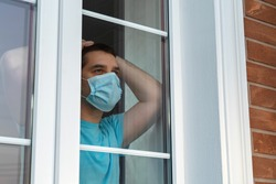 Home quarantine, self-isolation because of the Coronavirus disease, COVID-19. Man in a medical mask near the window. Boredom and depression during quarantine. Waiting for quarantine to be canceled.