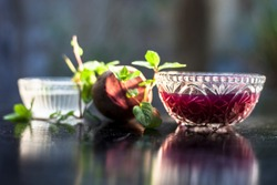Home remedy for dandruff on wooden surface i.e., beetroot stock well mixed with water in a glass bowl along with some freshwater and raw sliced beetroot. Horizontal shot with blurred creamy bokeh.