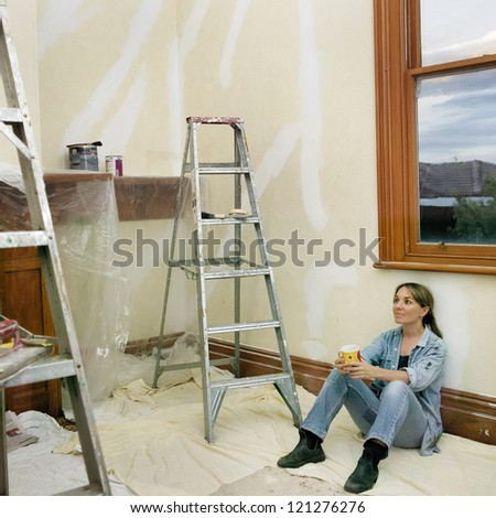 Home renovating, woman mid-thirties having a cup of tea during room painting
