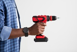 Home renovation, electric tool for job. Black man with smart watch holding electric drill, ready to work, standing over white background, side view, empty space, crop