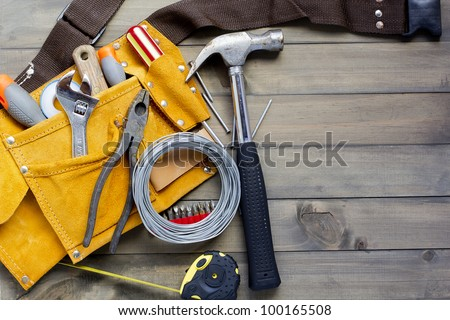 home renovation in progress. tool belt with various tools against wooden surface, add your text.