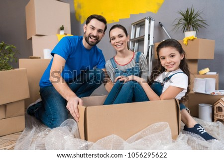 Home repair. Moving young family to new apartment. Repair in house for sale. Happy couple carries small daughter in box at house where repairs are being carried out. #1056295622