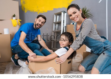 Home repair. Moving young family to new apartment. Repair in house for sale. Happy couple carries small daughter in box at house where repairs are being carried out. #1056295838