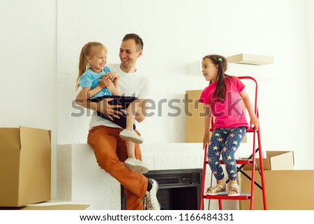 Home repair. Moving young family to new apartment. Repair in house for sale. Happy couple carries small daughter in box at house where repairs are being carried out. #1166484331
