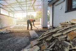Home repair. Rebuilding waterproofing and insulation of a terrace – roof, removal and stacking of the old insulating (polyurethane). Backlit worker with pickaxe