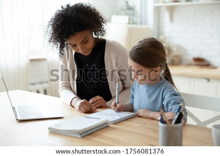 Home schooling conducted by parent or home tutor during quarantine time concept. African caring stepmom or nanny helps with school subject little daughter adorable kid girl, seated at table in kitchen Foto stock ©