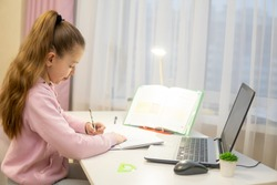 home-schooling. girl doing lessons in front of a laptop