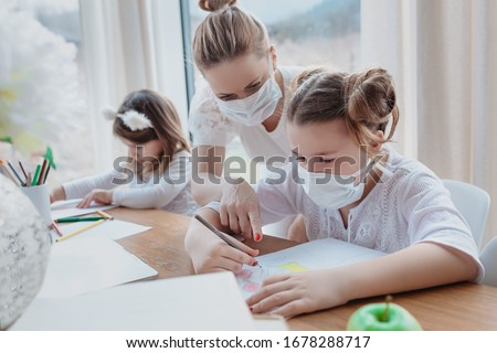 Home schooling learning during virus pandemic - pretty white woman with two children drawing in the living room, wearing surgical face masks to protect them from the virus.