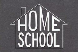 Home schooling word message on old grunge black chalkboard inside a house outline