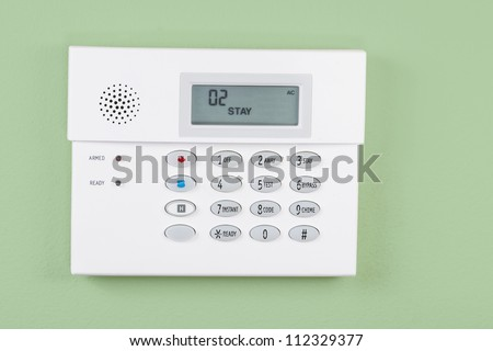 Home security alarm system activated on green wall background