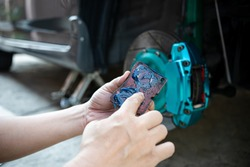Home service car concept : Close up hand a man Hold brake pads and applying Grease anti seize on the back brake pads in car caliper brake and check system in basic maintenance