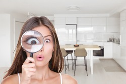 Home shopping funny inspection woman searching through magnifying glass at kitchen furniture. Deal hunting bargain hunter Asian girl looking at real estate new homeowner inspecting interior design.