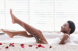 Home spa and relax on weekends. Cheerful millennial african american female in bathtub with foam and petals, raises legs and enjoys bathing in bathroom interior in morning, profile, copy space