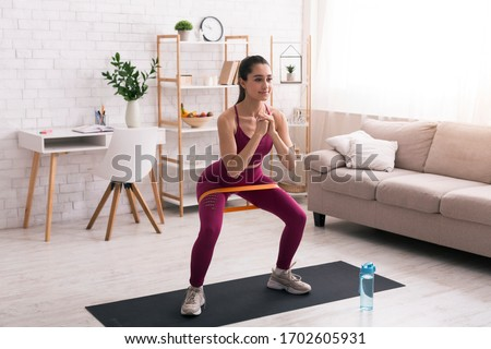 Home sports concept. Hispanic girl doing squats with elastic band in living room