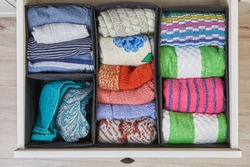 Home storage system for linen, clothes and fabrics. The drawer of the cabinet is divided into compartments using boxes of different sizes.Organizer for underwear and towels.