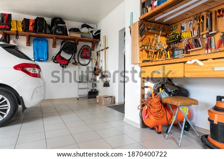 Home suburban car garage interior with wooden shelf, tools equipment stuff storage warehouse on white wall indoor. Vehicle parked at house parking background. DIY workbench for repair home appliances