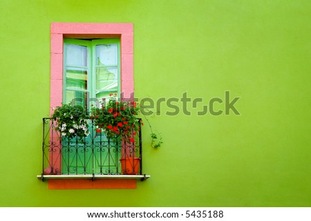 home sweet home: green window against a green wall - stock photo