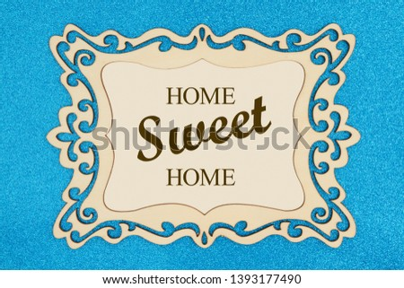 Home Sweet Home text on a retro wood picture frame on a blue glitter