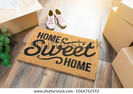 Home Sweet Home Welcome Mat, Moving Boxes, Pink Shoes and Plant on Hard Wood Floors.
