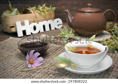 Home Tea Time Scene. Tea Cup With Lime Tree Herbal Green Tea, Honey, Herbs Leafs In The Basket, Clay Teapot, Vintage Spoon And Sign Home On Rustic Old Wooden Table