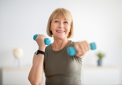 Home training concept. Strong senior woman doing exercises with dumbbells indoors. Cheerful mature lady working out her arm muscles, keeping fit, leading healthy lifestyle during covid-19 isolation