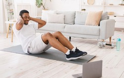 Home Training. Sporty African American Man Exercising Doing Sit-Ups Abs Exercise At Laptop Computer Indoors. Online Sport Workout, Morning Physical Training Exercises Concept