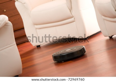 Home vacuum cleaning robot in action on genuine living room wooden floor. Selective focus on robot.