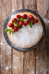 Home Victoria sponge cake, decorated with strawberries, cranberries and mint closeup on the table. vertical view from above