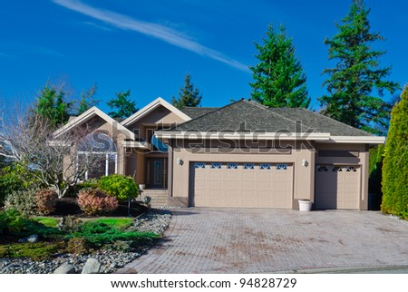 Home with covered entry and double three car garage with the dark blue sky in  Vancouver.