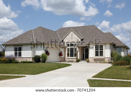 Home with stone entry and cream colored siding